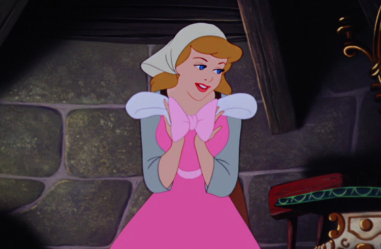 Cinderella is in her attic, holding a dress close to her chest and looking longingly to the right side of the image.