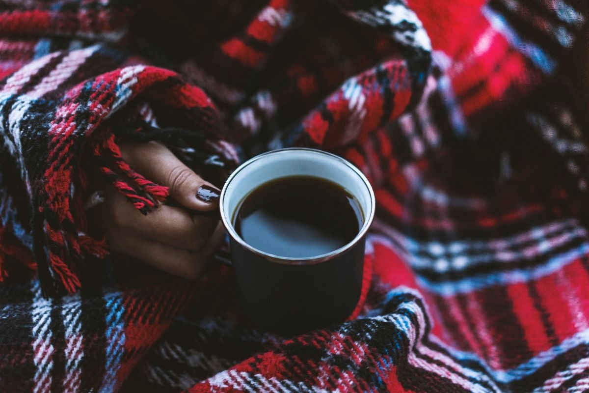 Someone wrapped in a flannel blanket and holding a mug of coffee