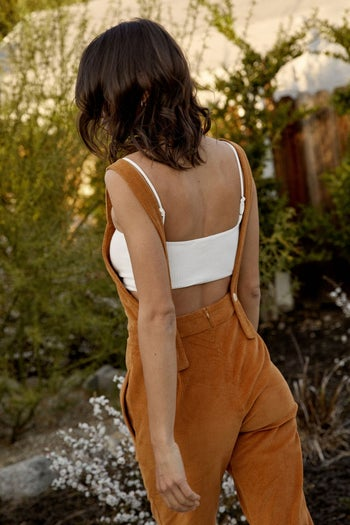 back view of a different model wearing the overalls in gold