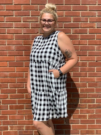 reviewer wearing the black and white gingham dress
