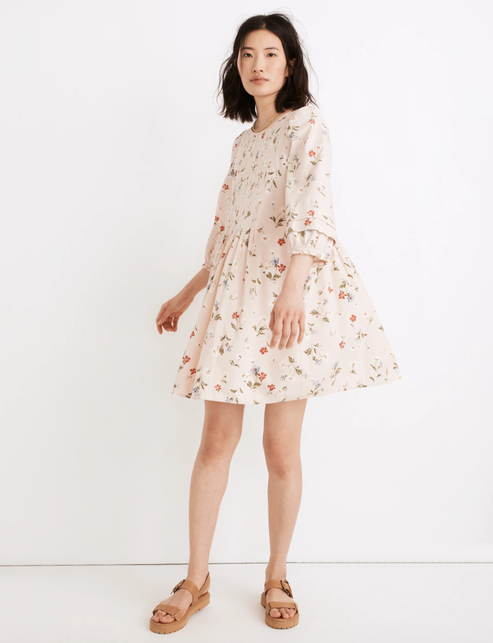 a model in a pale pink dress with puffy quarter sleeves and a floral print