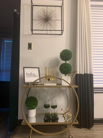 two-tiered bar cart with circle frame in gold holding decor in a reviewer's home