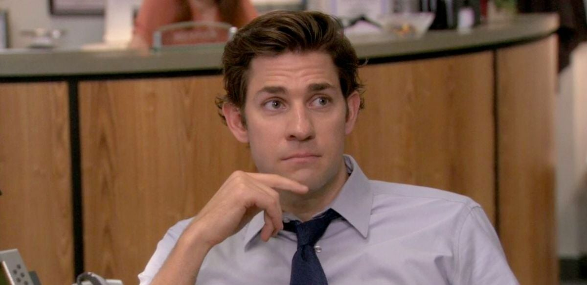 Jim Halpert is sitting at a desk with his index finger on his chin