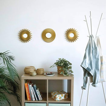 the mirrors in gold over a bookshelf