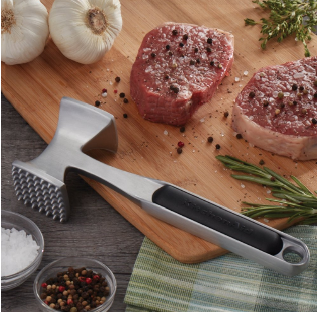 A metallic meat tenderizer on a wooden cutting board next to two slabs of meat and a white onion