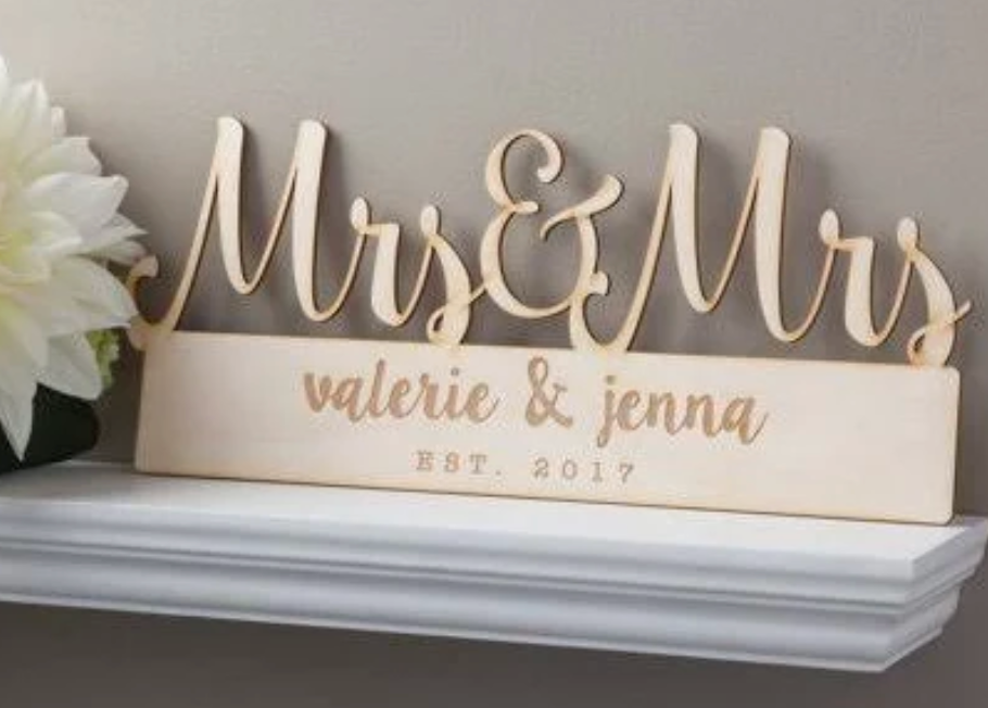 """A sign that says """"Mrs and Mrs"""" on a shelf on a wall"""
