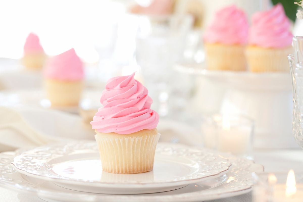 A vanilla cupcake with strawberry frosting