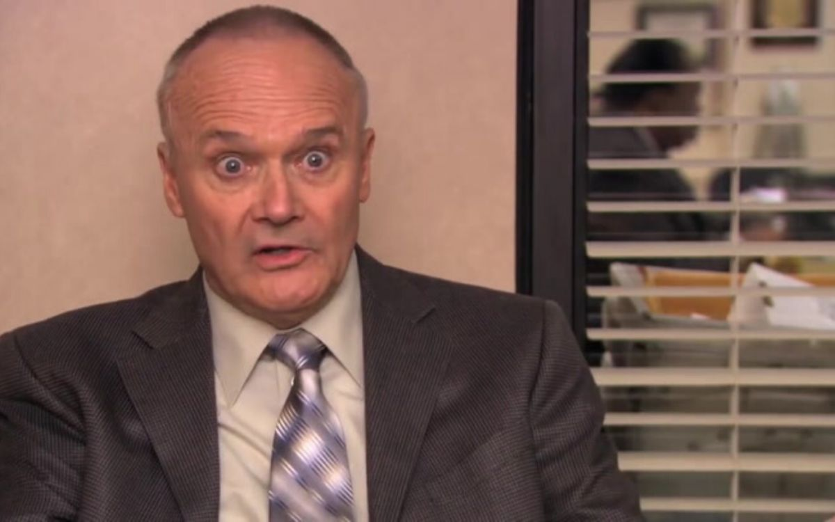 Creed Bratton is sitting at a chair with his eyes wide and blinds in the background