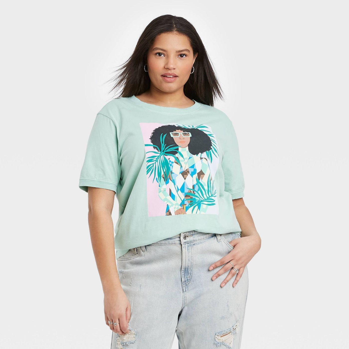 model wearing the teal t-shirt with illustration of a person with curly hair and square glasses holding a few palm leaves