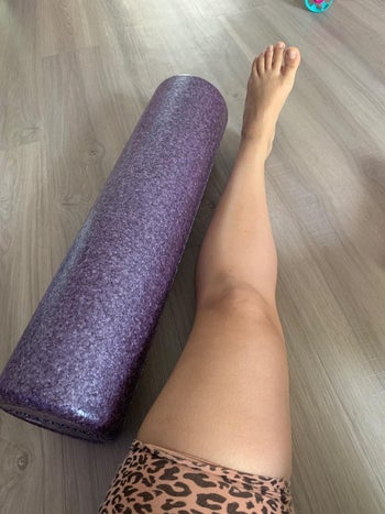 a reviewer photo with the foam roller next to a person's leg to show how long it is in a larger size