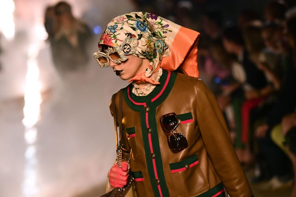 A model on a runway wears big sunglasses, a head scarf, and a leather jacket