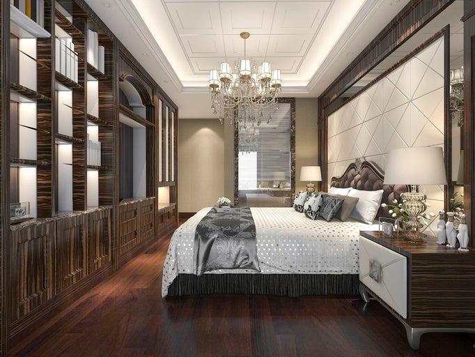 A bedroom with a wood floor and wooden cabinets all around the room, and a chandelier hanging above a plush bed with several throw pillows