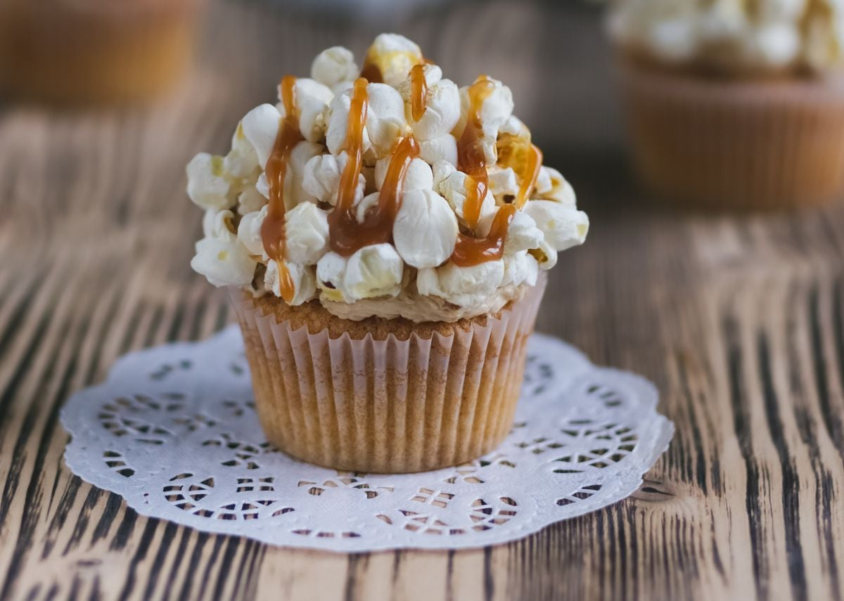 A cupcake topped with popcorn and caramel sauce