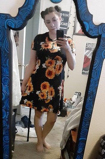 reviewer wears sunflower-print t-shirt dress while taking mirror selfie