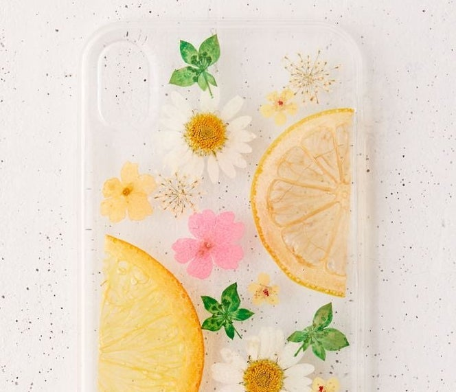 A clear phone case with flowers, leaves, and citrus fruits painted on it