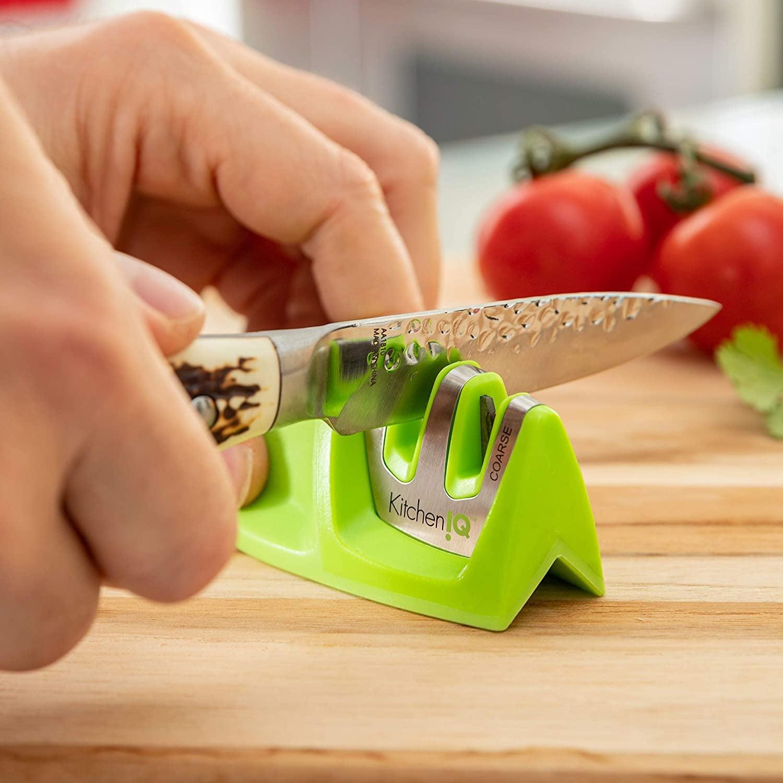 Hands running a knife through the small green sharpener