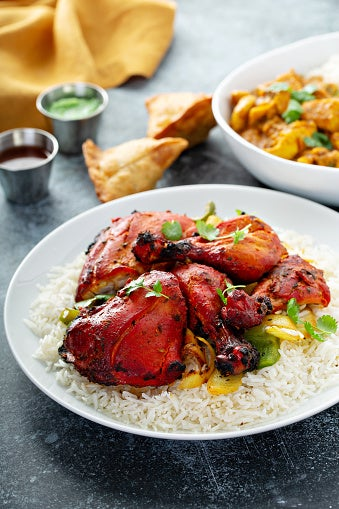 Tandoori chicken on a plate with plain rice and garnish