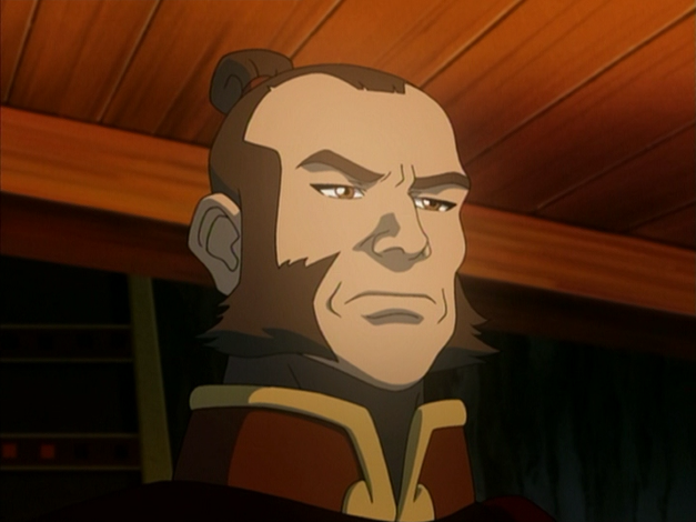A man with long sideburns and a bun in his hair looks stoic