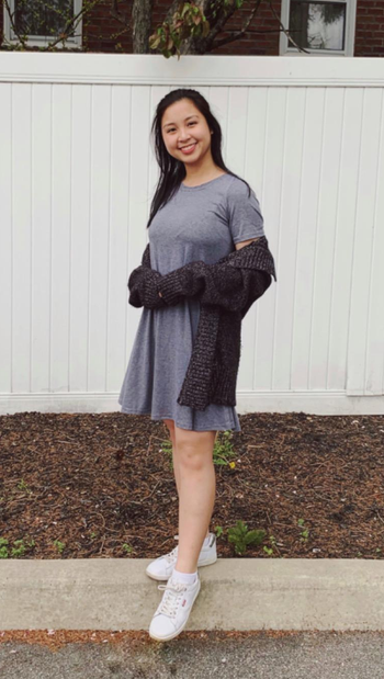 reviewer wears gray T-shirt dress with a black cardigan