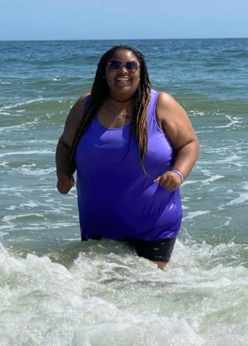 Reviewer wearing a purple tank top in the ocean
