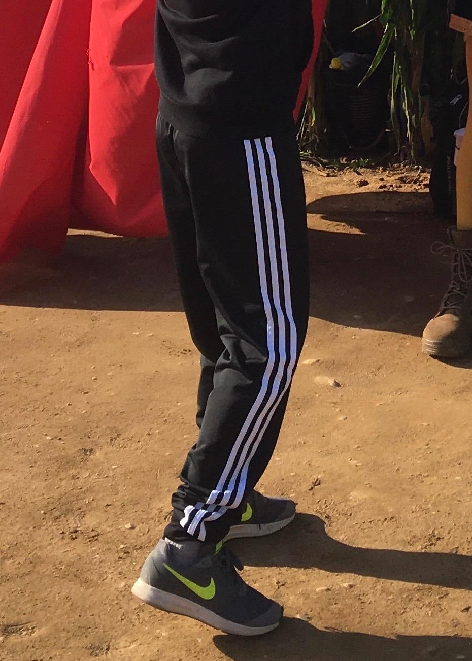 a reviewer's child in the black pants with three white stripes down the side of the leg
