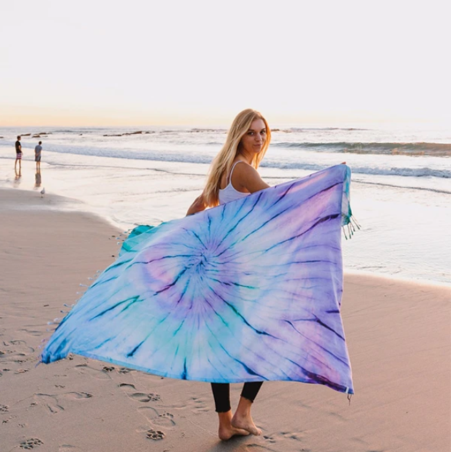 model holding the blue and purple towel while walking on the beach