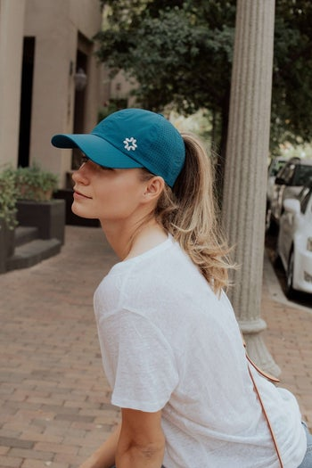 Model in a blue baseball cap with a high ponytail coming out of the back