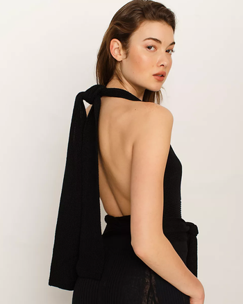 Model wearing the tank in black with the straps tied in a halter