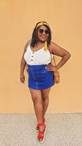 reviewer wearing the white version with a denim skirt and red sandals