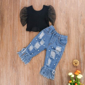 a black blouse with puffy sleeves and ripped jeans with fringe at the bottom