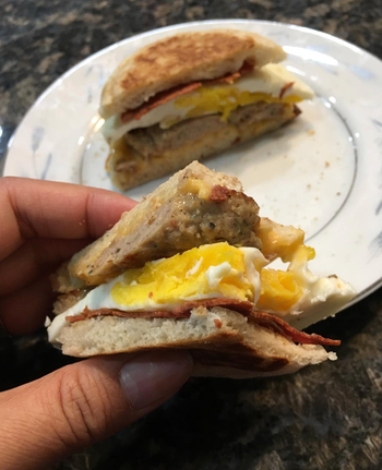 reviewer holding the bacon egg and cheese