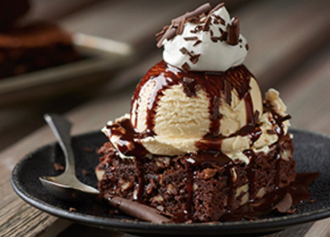 A walnut brownie topped with vanilla ice cream, chocolate sauce, and whipped cream