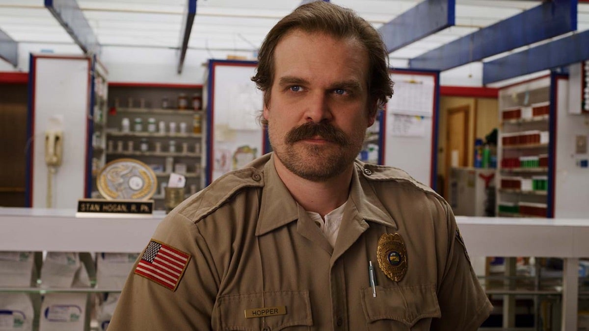 Hopper is standing with his uniform on