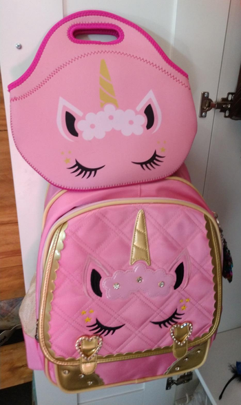 a reviewer's photo of the pink unicorn backpack and matching lunch box