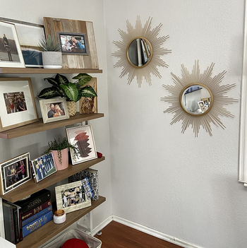 a reviewer photo of a pair of mirrors hung on the wall next to a bookshelf