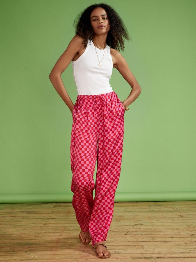 Model wearing bright pink checkerboard trousers with tan sandals and a white tank top