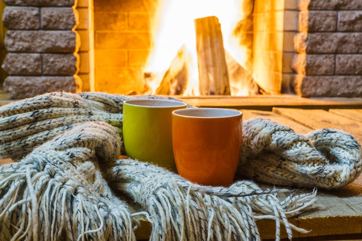 A fireplace with two mugs and a blanket in front of it