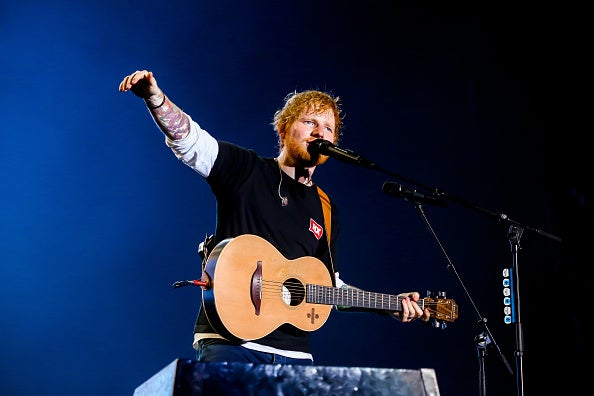 Ed Sheeran stands on his stage with his guitar during a concert.