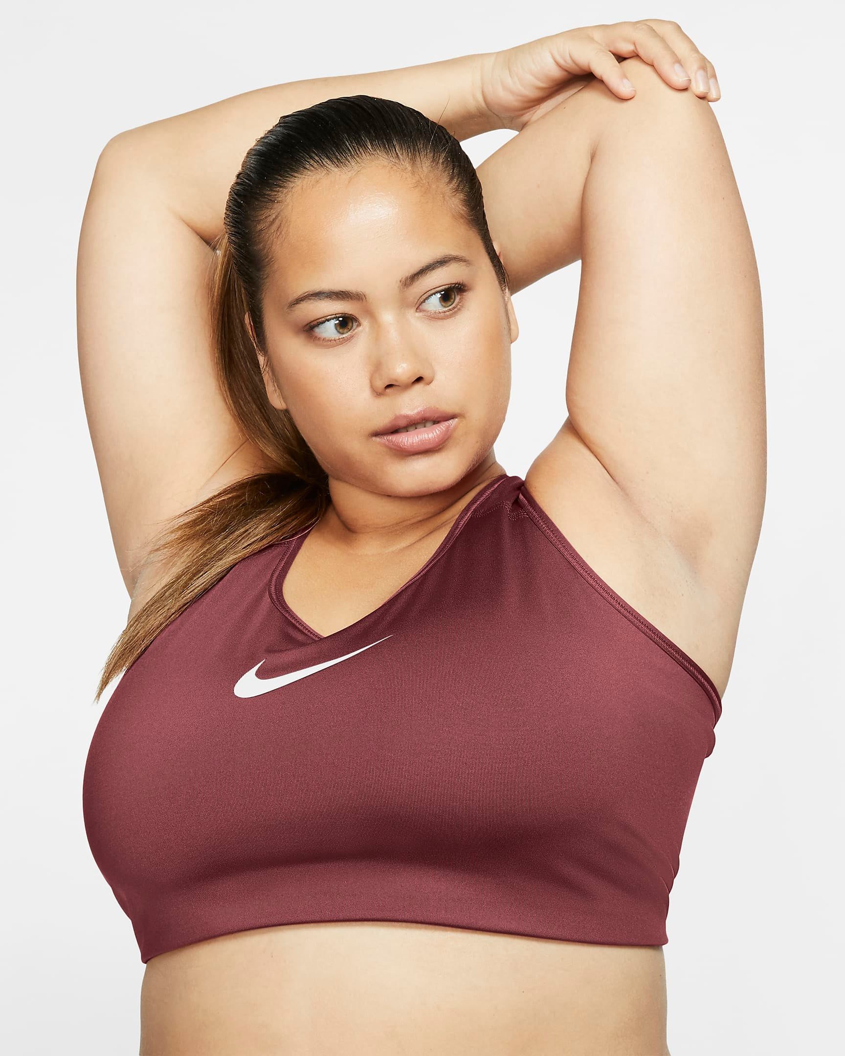 model wears berry-tone Nike medium-support sports bra