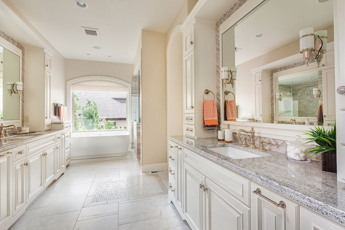 A bright, large bathroom with counters with a sink on either side and a large bathroom towards the end of the room