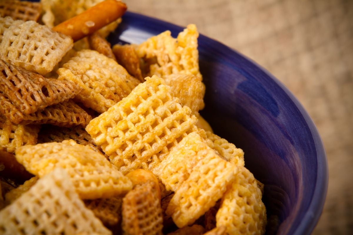 Chex cereal pieces, pretzels, and small breadsticks in a bowl