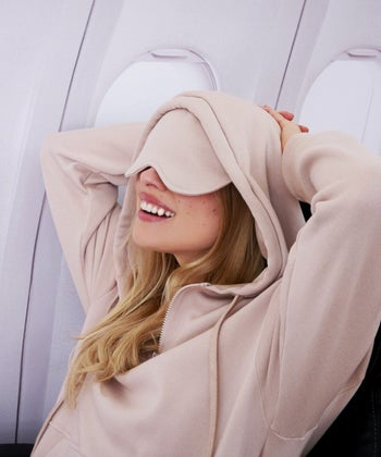 model wearing a hoodie with built in sleeping mask on a flight