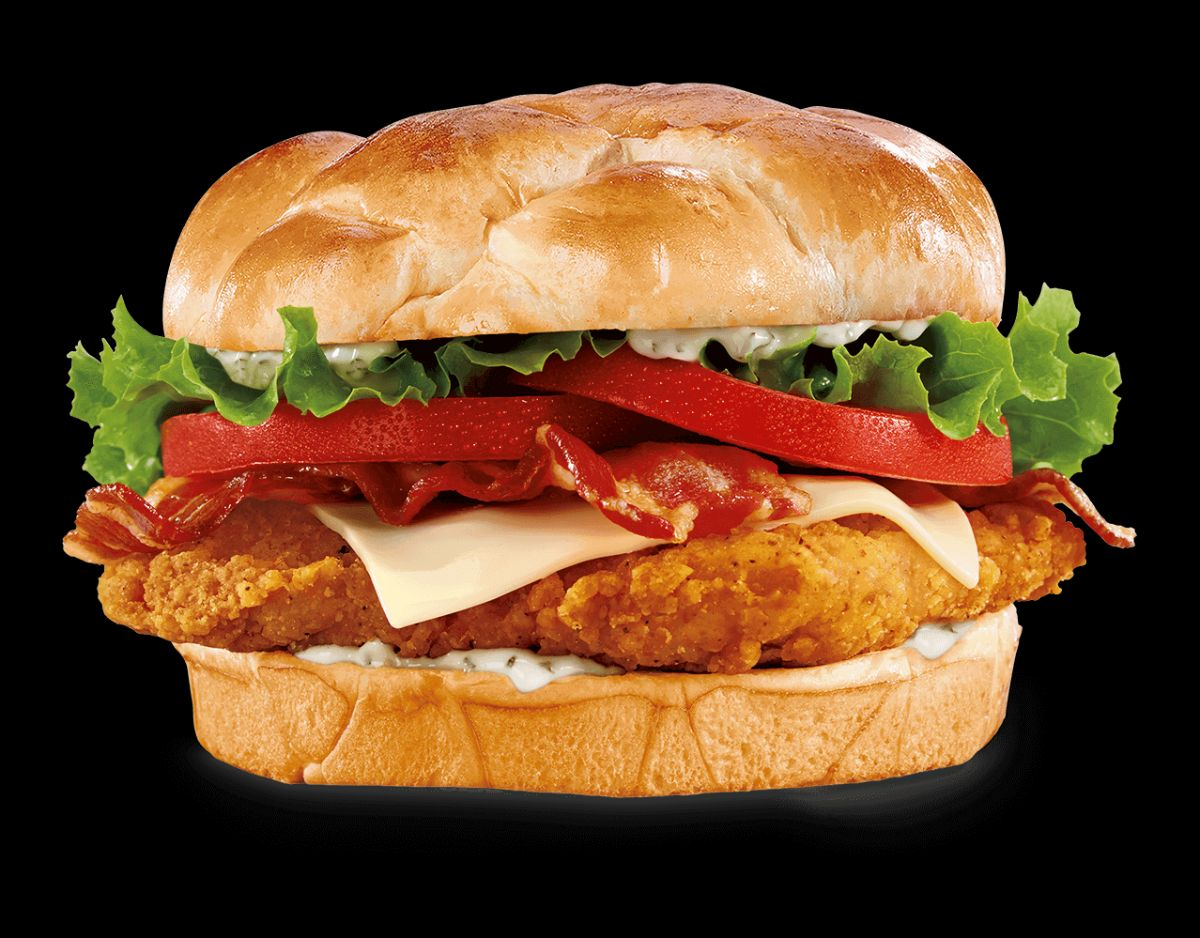 A crispy chicken sandwich with Swiss cheese, bacon, lettuce, tomatoes, and ranch