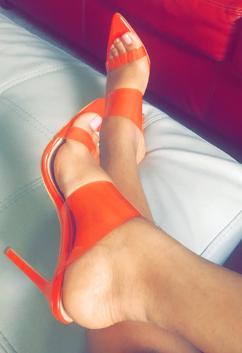 reviewer wearing transparent bright orange heels
