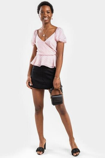 model wearing the pink blouse with a black skirt and heels