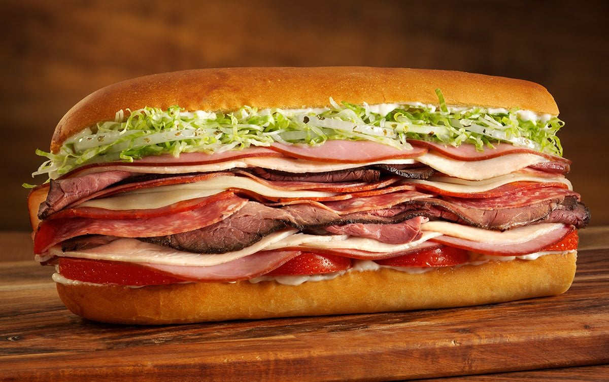 A large sandwich with turkey, ham, roast beef, salami, mayo, cheese, lettuce, and tomato