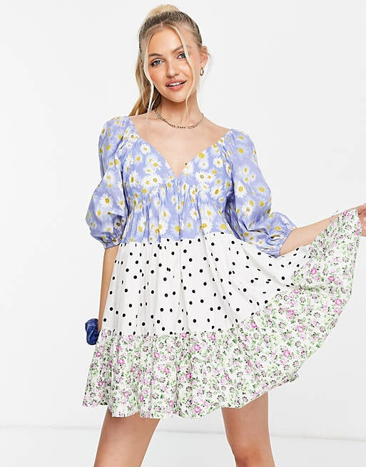 reviewer wearing the voluminous elbow sleeve babydoll dress with tiers in blue and white daisy, black and white polka dot, and white, green, and pink floral prints
