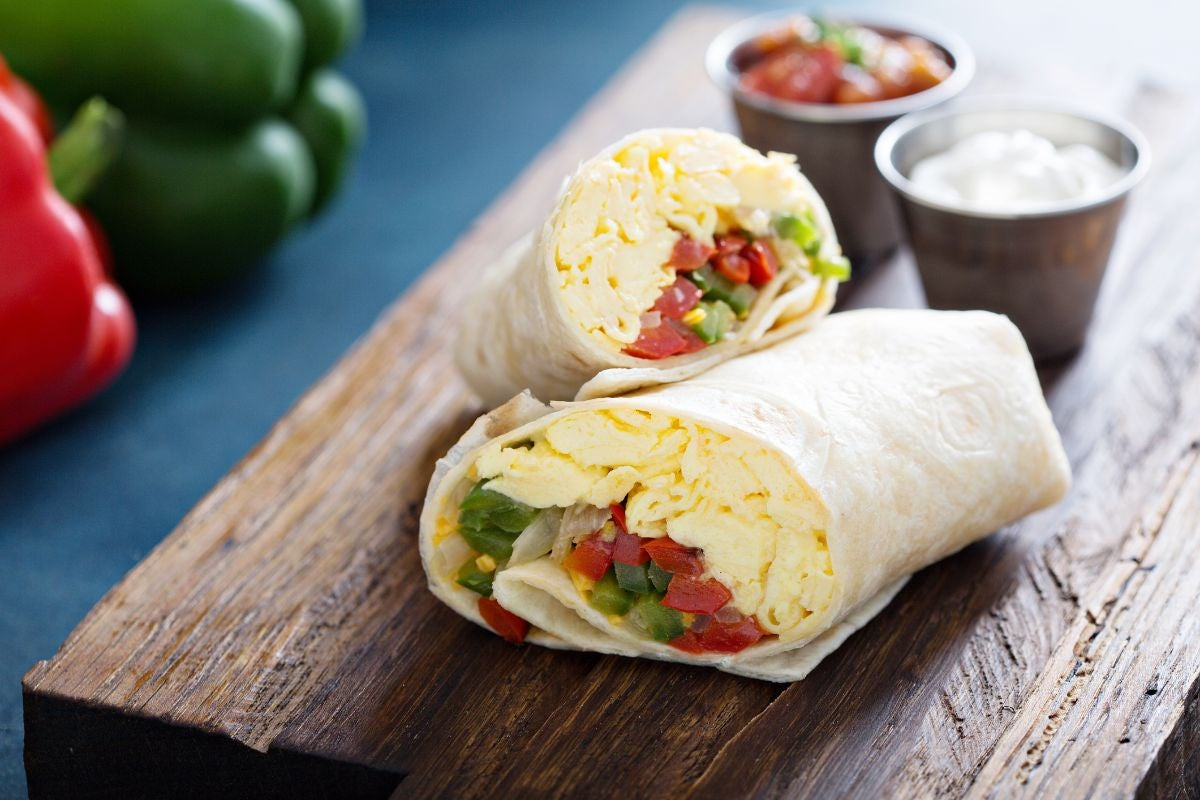 A burrito stuffed with scrambled eggs, onions, and bell peppers