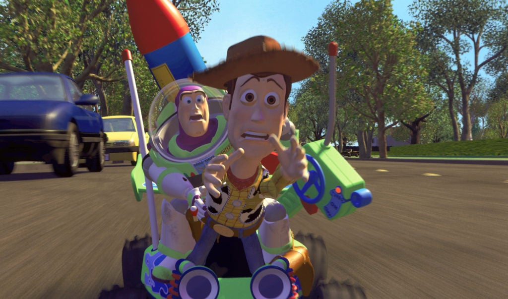 Woody and Buzz ride down the neighborhood street on a toy car
