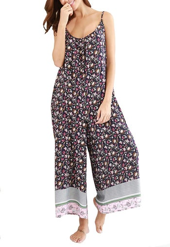 a model wearing the jumpsuit in black floral